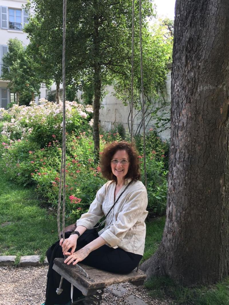 Woman with dark hair and glasses sitting on a swing in a garden courtyard