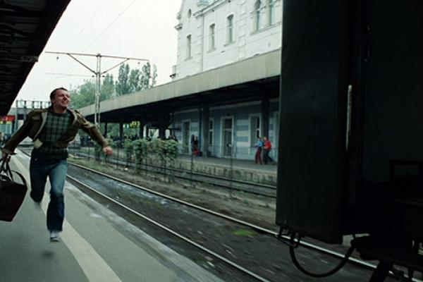 Man running to a platform to catch a leaving train