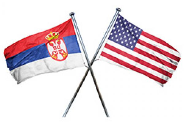 US flag hanging to the right, Serbian flag crossed over hanging to the left