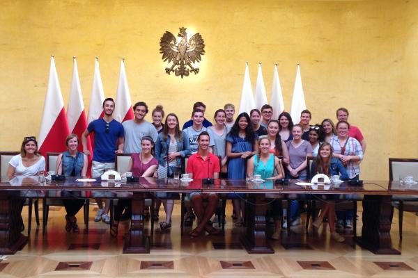 Two rows of students sitting underneath Polish government seal