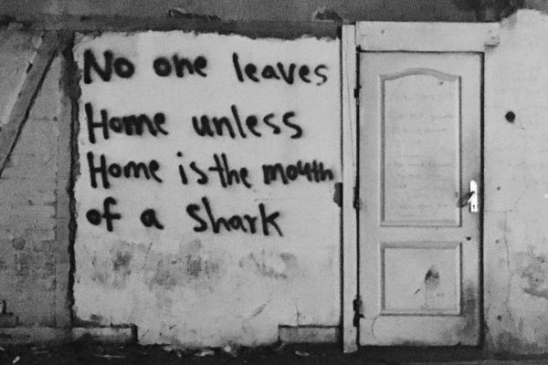 No One Leaves Home Unless Home is the Mouth of a Shark graffiti on a building